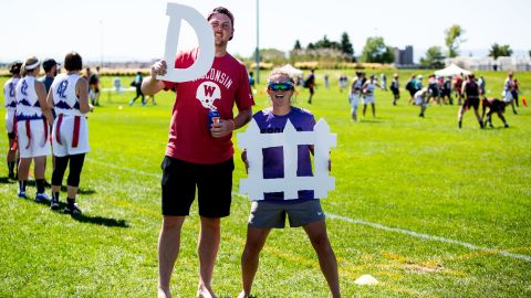 Fans pose with homemade signs spelling -- spelling defense -- on the sideline.