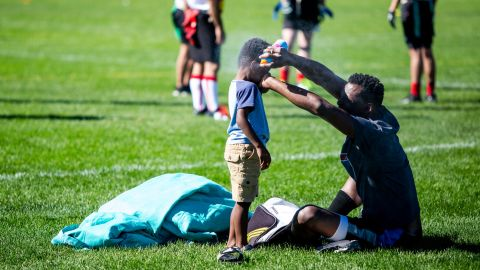 A player sprays his son with sunscreen to protect him from the scorching weather in Denver.