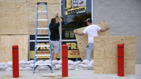 Justin Davis, left, and Brock Mclean board up a business in Destin, Florida, on Tuesday, October 9.