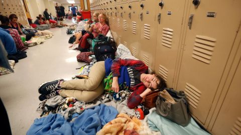 Emily Hindle lies on the floor at an evacuation shelter set up at a Panama City Beach high school on October 10.