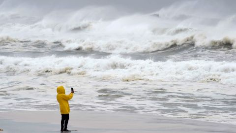 A person takes pictures of the surf and fishing pier on Okaloosa Island in Fort Walton Beach, Florida.