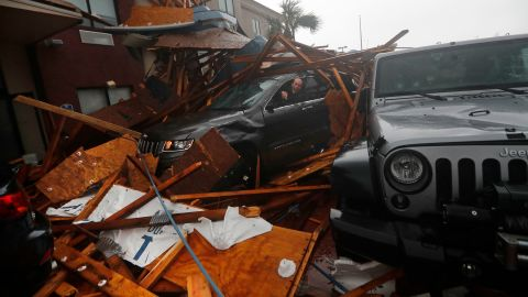 A storm chaser climbs into his vehicle to retrieve equipment after a hotel canopy collapsed in Panama City Beach on October 10.