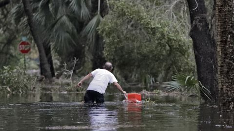 A resident of St. Marks, Florida, pulls a cooler out of the floodwaters near his home.