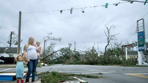A woman and her children wait near a destroyed gas station in Panama City on October 10.