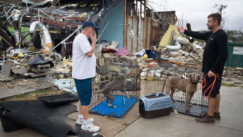 Rick Tesk, left, helps a business owner rescue his dogs from a damaged business in Panama City.