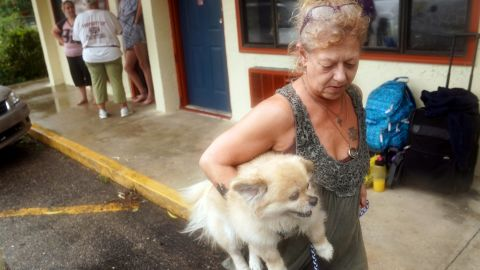 Lenora Adams evacuates a motel with her dog as the hurricane comes ashore in Panacea, Florida, on October 10.