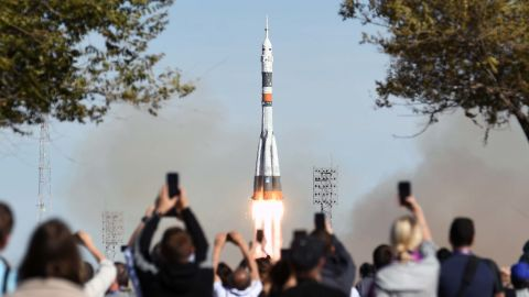 A crowd watches as the Soyuz-FG rocket booster lifts off from the Baikonur Cosmodrome. Dramatic footage minutes later showed the capsule carrying the crew as it parachuted back to Earth before thumping down in a plume of dust in Kazakhstan, about 250 miles away from where it took off.<br />