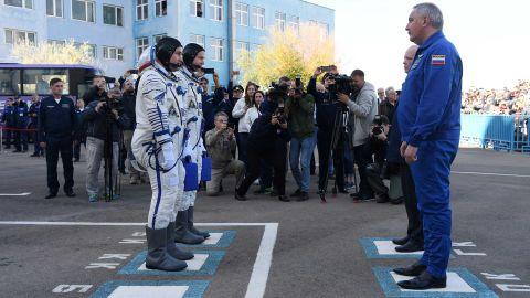 Nick Hague and Alexey Ovchinin report to Roscosmos head Dmitry Rogozin before boarding the Soyuz MS-10 spacecraft.