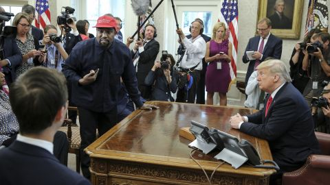 Rapper Kanye West, second left, stands up as he speaks during a meeting with U.S. President Donald Trump in the Oval office of the White House on October 11, 2018 in Washington, DC.