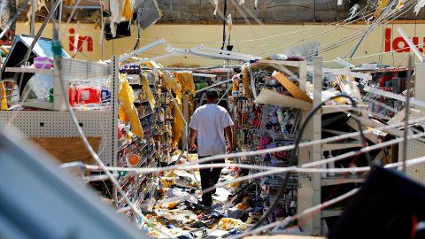 A man walks through a damaged store in Springfield, Florida.