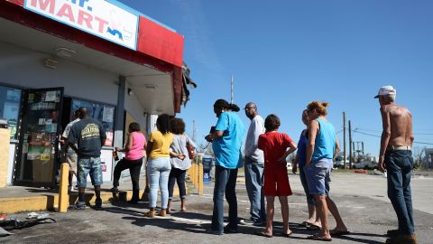 People line up Friday outside a Panama City convenience store in the aftermath of Hurricane Michael.