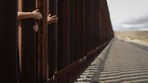 People reach through the wall from the Mexican side at the conclusion of the Hugs Not Walls event on the U.S.-Mexico border on October 13, 2018 in Sunland Park, New Mexico. More than 200 families with mixed immigration status living in the U.S. were allowed to reunify with relatives in Mexico for three minutes after Border Patrol briefly opened the border wall to allow the reunions. The event is approved by the U.S. government as families keep their feet on their respective sides of the border. The event is normally held in downtown El Paso but was moved to New Mexico due to new construction of an 18-foot border wall in El Paso.