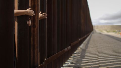 People reach through the wall from the Mexican side at the conclusion of the Hugs Not Walls event on the U.S.-Mexico border on October 13, 2018 in Sunland Park, New Mexico. More than 200 families with mixed immigration status living in the U.S. were allowed to reunify with relatives in Mexico for three minutes after Border Patrol briefly opened the border wall to allow the reunions.