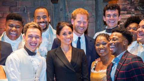 """Meghan and Harry pose with the cast and crew of the musical """"Hamilton"""" after a performance in London in August 2018. Harry gave those in the theater something to remember after <a href=""""https://www.cnn.com/2018/08/30/uk/prince-harry-meghan-markle-hamilton-intl/index.html"""" target=""""_blank"""">breaking into mock-song</a> at the end of the show. The show was held to raise money for his HIV charity, Sentebale."""