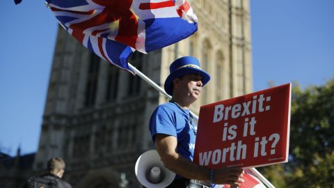 """Anti-Brexit campaigner Steve Bray stands outside parliament with EU and Union Flags and a placard that reads """"Brexit: is it worth it?"""" as he protests in Parliament Square in London on October 9, 2018. (Photo by Tolga AKMEN / AFP)        (Photo credit should read TOLGA AKMEN/AFP/Getty Images)"""