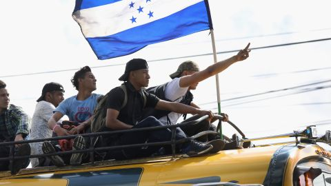 Migrants display the flag of Honduras while on a caravan of migrants en route to the Mexican border on Thursday in Guatemala City. The caravan of thousands of Central Americans, most from Honduras, hopes to eventually reach the United States. President Donald Trump has threatened to cancel the recent trade deal with Mexico and withhold aid to Central American countries if the caravan isn't stopped before reaching the United States.