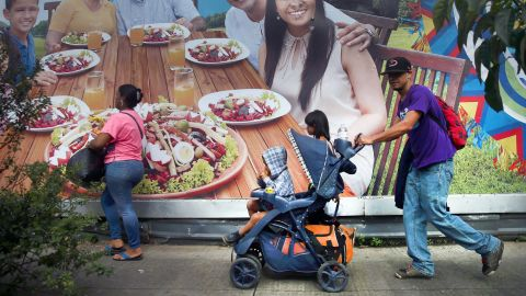 A Honduran migrant, part of a caravan trying to reach the United States, pushes a stroller with a boy during a new leg of their travel in Guatemala City on Thursday.