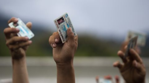 Honduran migrants holds up their national ID cards as Guatemalan police block them and their caravan after the group crossed the Honduras-Guatemala border in Esquipulas, Guatemala, on Monday, October 15, 2018. Police stopped the migrants for several hours but the travelers refused to return to the border and were eventually allowed to pass.