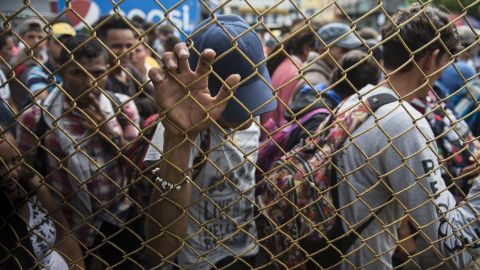 Honduran migrants wait outside the border between Guatemala and Mexico, in Tecun Uman, Guatemala, Friday, Oct. 19, 2018. Thousands of migrants traveling in a caravan briefly moved toward a border crossing on the Mexico-Guatemala frontier before turning around. Guatemala has closed its border gate and is standing guard with dozens of troops and two armored jeeps.