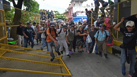 Honduran migrants heading in a caravan to the United States rush through the Guatemala-Mexico border bridge after tearing down its gate in Ciudad Hidalgo, Mexico, on Friday, October 19.