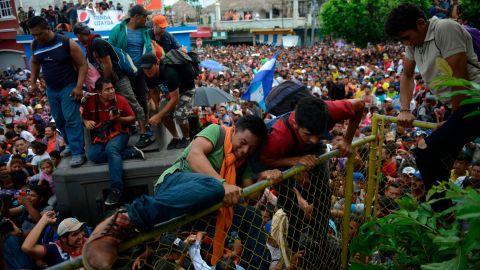 Thousands of Honduran migrants rush across the border toward Mexico, in Tecun Uman, Guatemala, Friday, October 19.