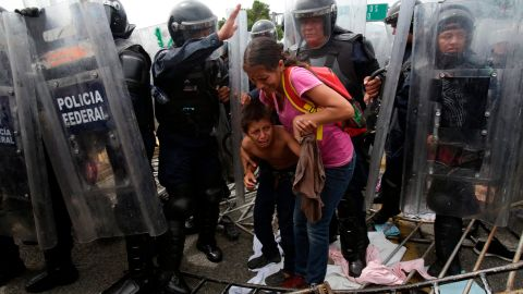 A Honduran migrant mother and child are surrounded by Mexican Federal Police in riot gear, at the border crossing in Ciudad Hidalgo, Mexico, Friday, October 19.
