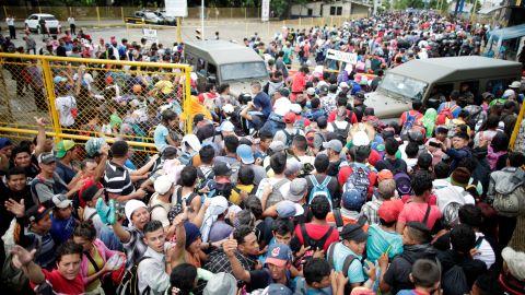 Honduran migrants, part of a caravan trying to reach the United States, storm a border checkpoint to cross into Mexico, in Tecun Uman, Guatemala, Friday, October 19.