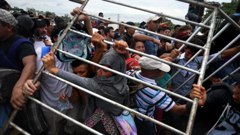 Honduran migrants heading in a caravan to the United States remove a barrier at the Guatemala-Mexico border bridge in Ciudad Hidalgo, Mexico, on Friday, October 19.