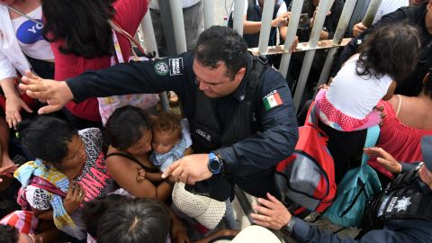 Mexican federal police officers allow women and children taking part in a caravan of Honduran migrants heading to the United States to cross to Mexico in the border city of Tecun Uman, Guatemala, on Friday, October 19.