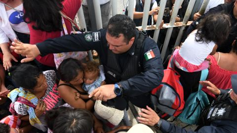 Mexican federal police officers allow women and children, taking part in a caravan of Honduran migrants heading to the US, to cross to Mexico in the border city of Tecun Uman, 257 kilometers south of Guatemala City, on October 19, 2018. - Honduran migrants who have made their way through Central America were gathering at Guatemala's northern border with Mexico on Friday, despite President Donald Trump's threat to deploy the military to stop them entering the United States.