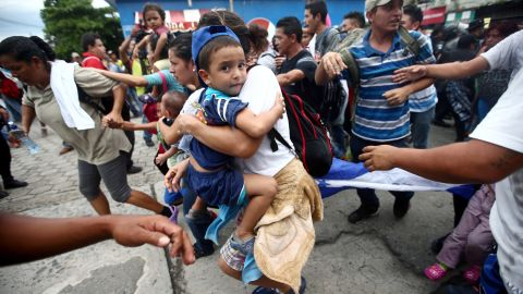 A Honduran migrant, part of a caravan trying to reach the United States, storms the checkpoint between Guatemala and Mexico in Tecun Uman, Guatemala, Friday, October 19.