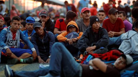 Migrants in the caravan wait on Saturday for the opening of the gate on the bridge that connects Guatemala to Mexico.