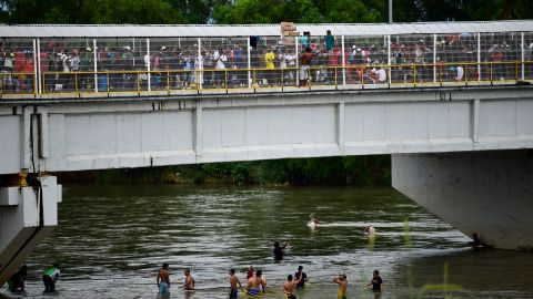 Honduran migrants help some of their members get down to the Suchiate River from the Guatemala-Mexico border bridge in Ciudad Hidalgo on Saturday.