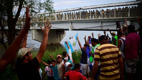 Honduran migrants who have already reached Mexican soil cheer at the rest of the group still waiting to cross at the Guatemala-Mexico border bridge in Ciudad Hidalgo, Mexico, on Saturday, October 20.
