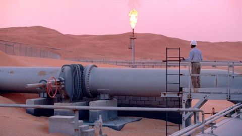 """SHAYBAH, SAUDI ARABIA - MARCH 2003:  A worker stands at a pipeline, watching a flare stack at the Saudi Aramco oil field complex facilities at Shaybah in the Rub' al Khali (""""empty quarter"""") desert on March 2003 in Shaybah, Saudi Arabia. (Photo by Reza/Getty Images)"""