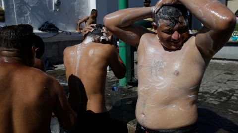 Migrant men bathe using water from a fire hydrant at the main plaza in Tapachula, Mexico.