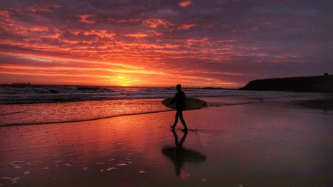 <strong>\North Tyneside, United Kingdom</strong>: A surfer heads toward the North Sea at sunrise in North Tyneside in northern England.
