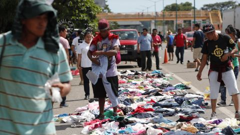 Migrants select clothes that have been placed along the road by Mexican citizens.