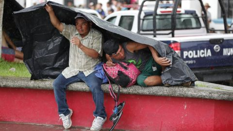 Migrants take shelter from the weather under a tarp as they rest in the town of Huixtla, Mexico, on October 22.