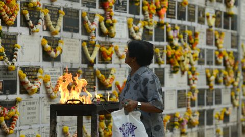 A woman prays near a plaque commemorating relatives on All Souls Day at a cemetery in Mumbai, India, on November 2, 2017. All Souls Day is observed in remembrance of friends and loved ones who passed away.