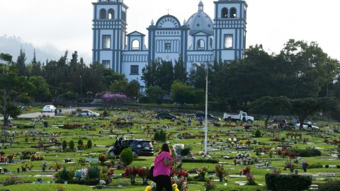 A woman takes flowers to the grave of a relative during the Day of the Dead at a cemetery in Tegucigalpa, Honduras, on November 2, 2017.
