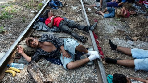 Migrants heading in caravan to the United States rest on the train tracks in Arriaga, Mexico.