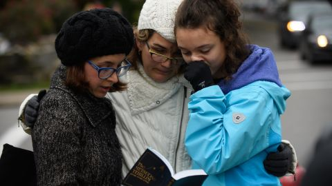 Tammy Hepps, Kate Rothstein and her daughter, Simone Rothstein, 16, pray from a prayerbook a block away from the site of a mass shooting at the Tree of Life Synagogue in the Squirrel Hill neighborhood on October 27, 2018 in Pittsburgh, Pennsylvania.