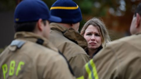An unidentified woman asks for a status update from firefighters a block away from the shooting.