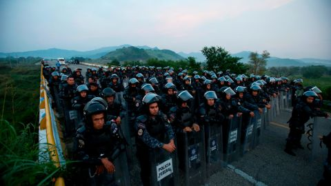 Police in riot gear block the highway to stop a caravan of thousands of Central American migrants from advancing through Mexico on Saturday.