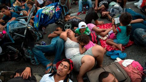 Migrants rest on a road between the Mexican states of Chiapas and Oaxaca after federal police briefly blocked them outside the town of Arriaga on Saturday, October 27.