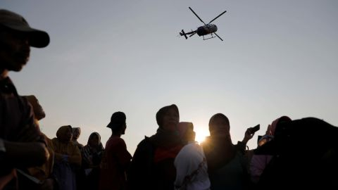 People watch a rescue team as a helicopter flies overhead.