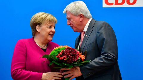 Merkel offers flowers to Volker Bouffier, the state premier of Hesse and the deputy chairman of the Christian Democratic Union, ahead of a party leadership meeting in October 2018. The day before, her coalition government suffered heavy losses in a key regional election in Hesse.