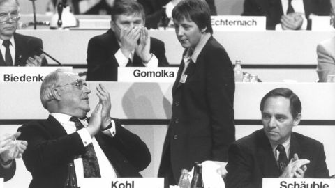 Merkel looks at Kohl during a conference of the Christian Democratic Union, their political party, in 1991. At the time, Merkel was a deputy chairwoman for the party.