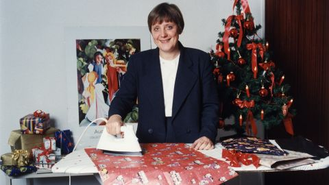 Merkel, as the country's leader on environmental issues, irons wrapping paper to show how it can be recycled.
